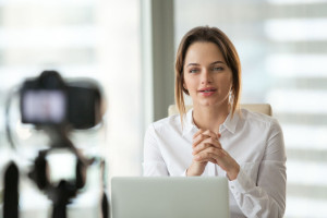 Successful businesswoman vlogger or coach talking to camera film